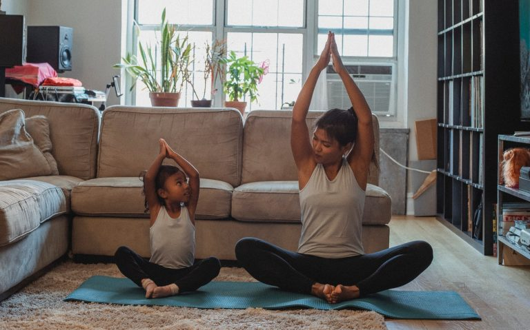 woman and daughter practicing yoga