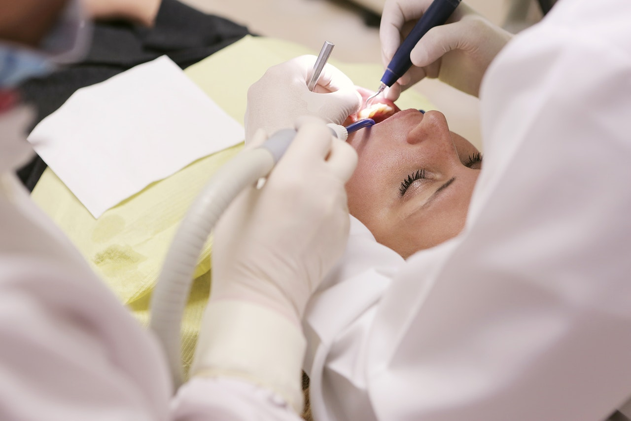 dentists cleaning a woman's teeth
